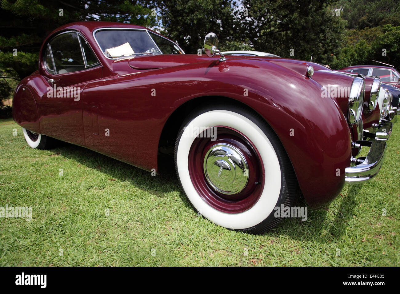 stock photo vintage maroon jaguar xk140 with white wall tires