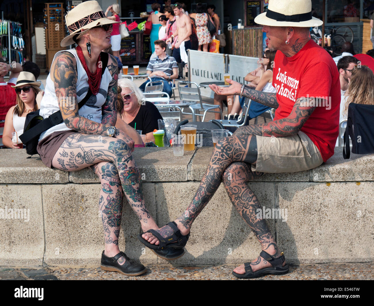heavily tattooed people chat close to the seafront at