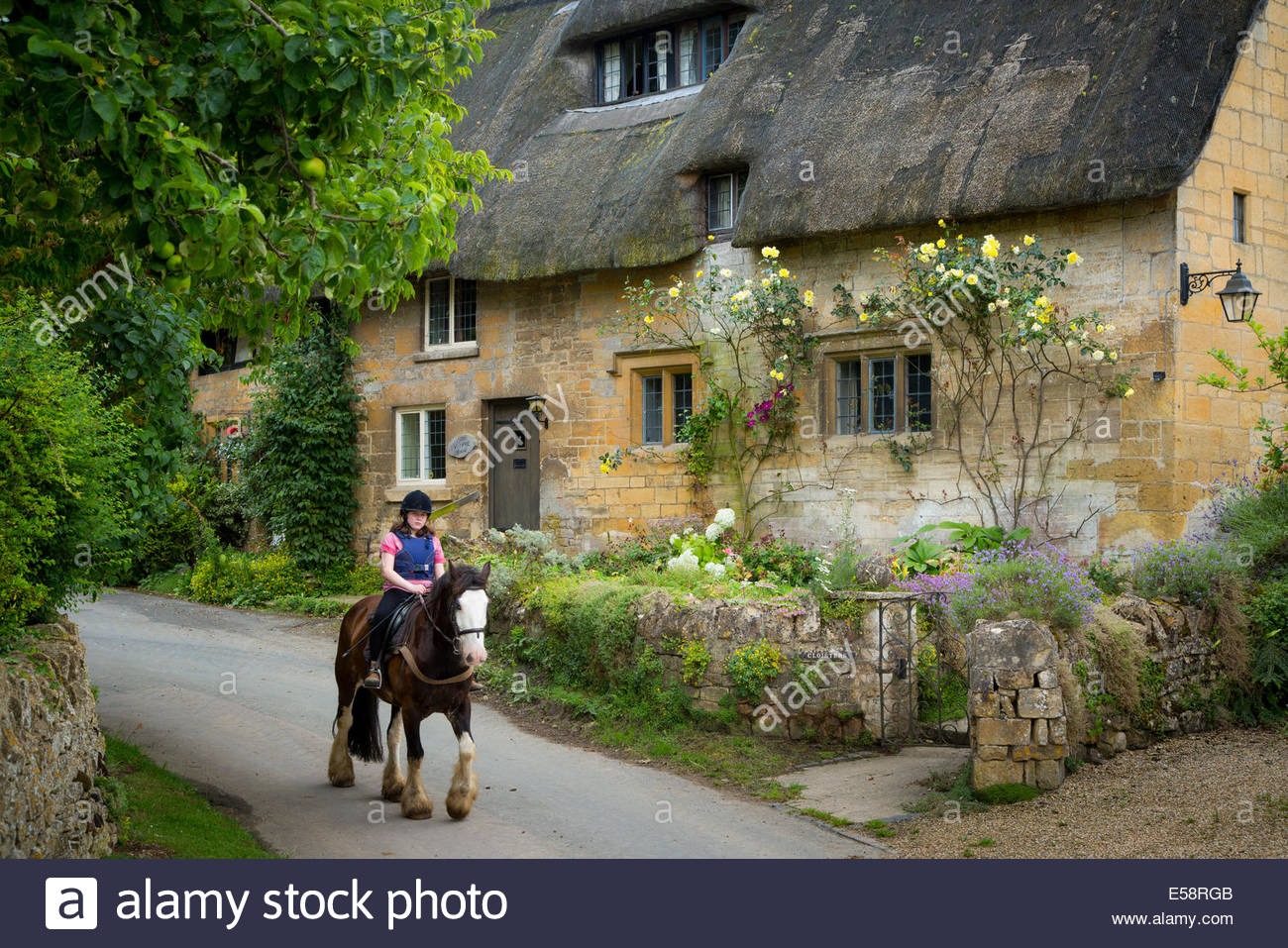 Girl On Horseback Below Thatched Roof Cottage Stanton The Cotswolds Gloucestershire England