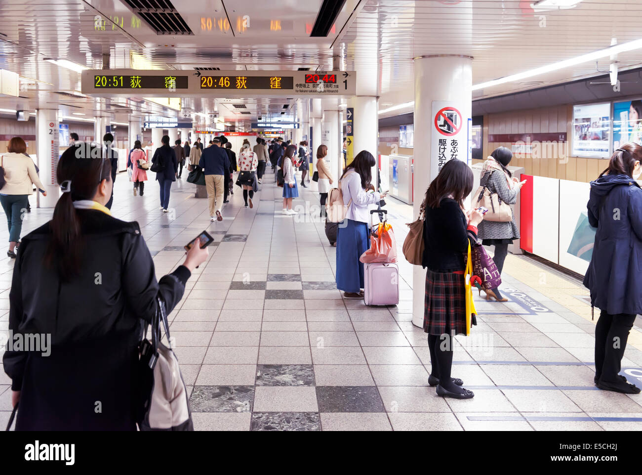 People waiting for a train on a Tokyo Metro subway station ...