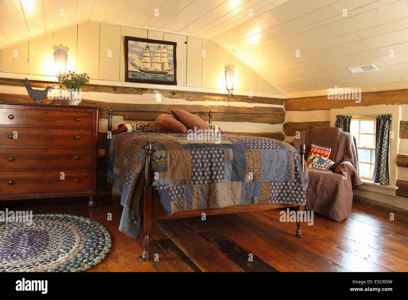 log cabin attic bedroom with exposed logs and hardwood floors usa