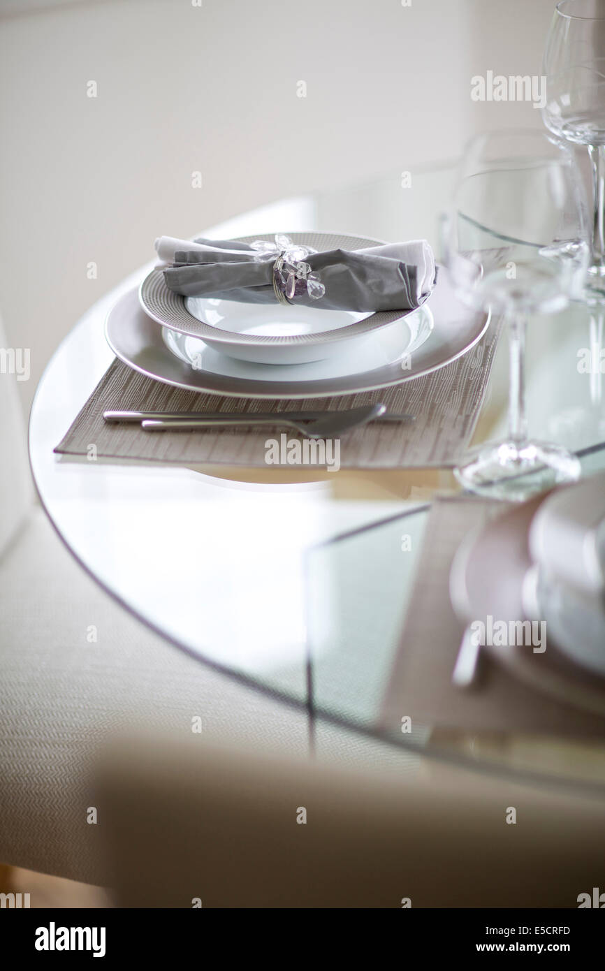 Close up of dinner setting on glass dining table in British home ...