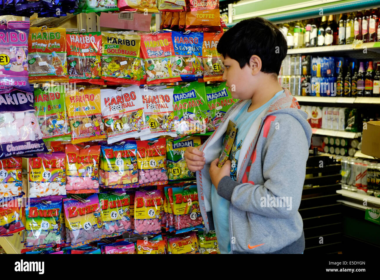 young boy shoplifting sweets in a small mini market Stock ...