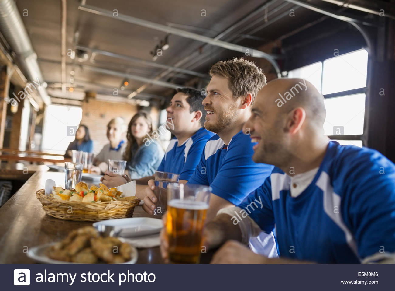 Fans taking pictures with cell phone behind barrier stock photo - Sports Fans Sitting At Bar In Pub Stock Image