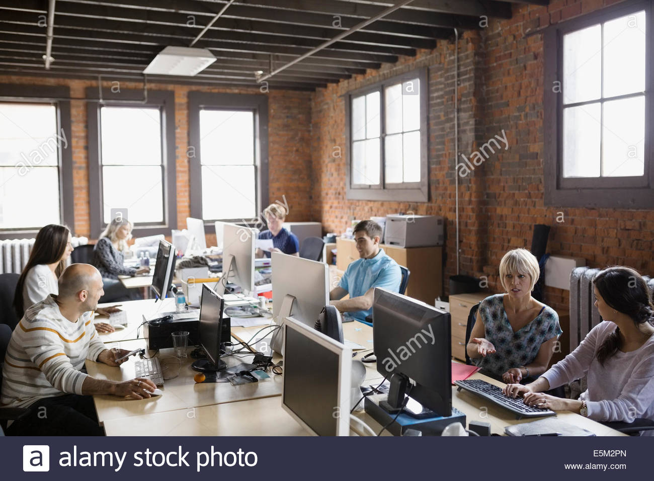 Business people working at computer workstations in office ...