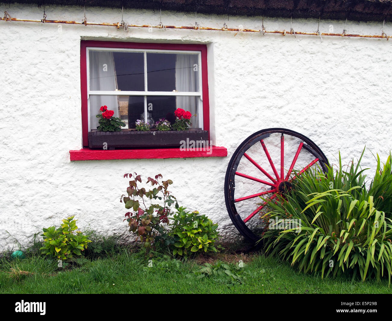 Exterior Of A Traditional Irish Cottage With Red Painted Window And Old Cart Wheel
