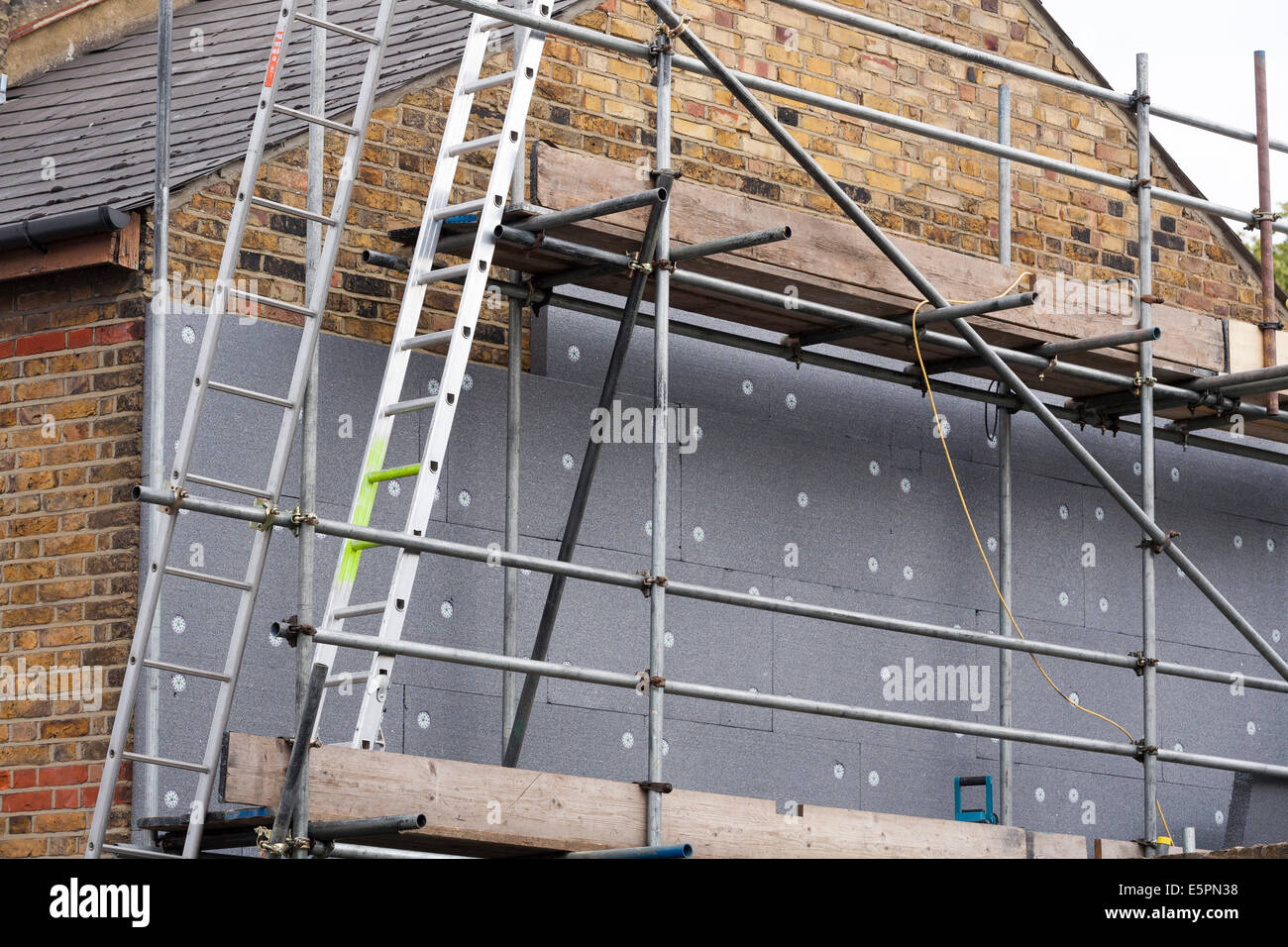 builders attaching fitting rigid foam wall insulation sheets panels boards to the gable