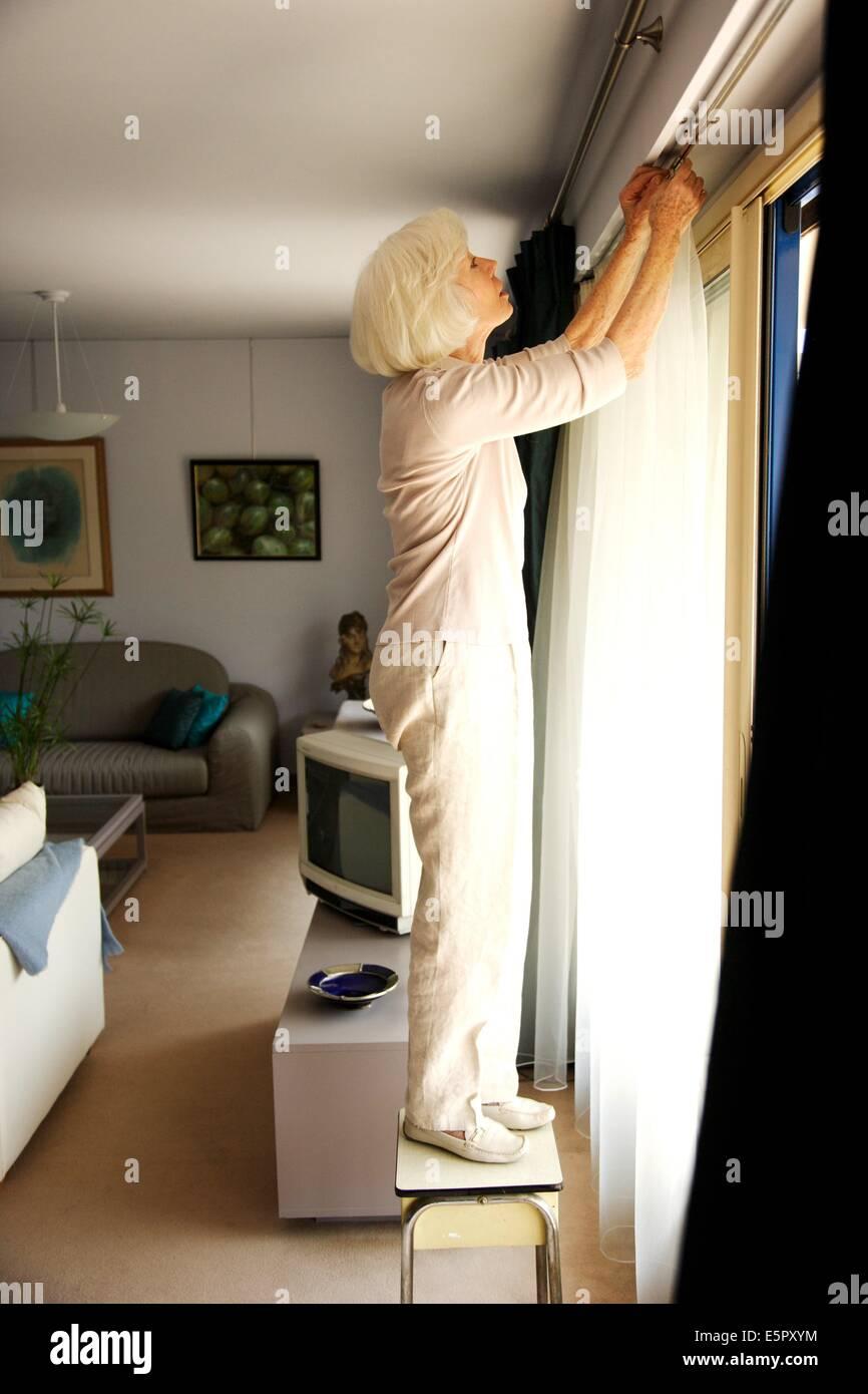 Elderly Woman Installing Curtains.