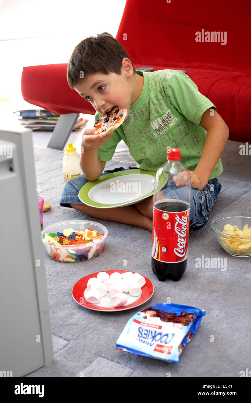 kids watching tv and eating. child snacking while watching tv. kids tv and eating w