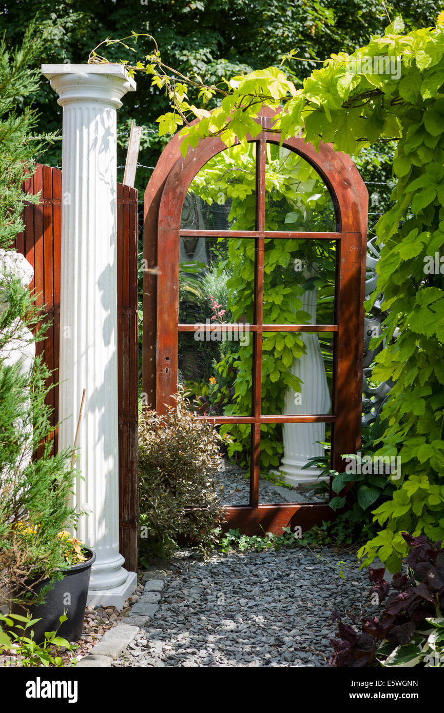 A mirror in a small courtyard garden creating the illusion for Creating a courtyard garden