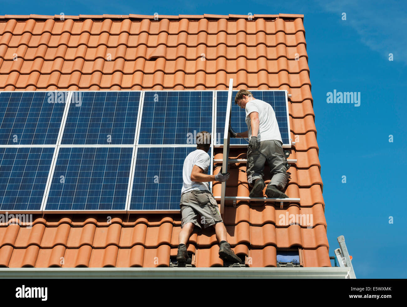 Stock Photo   Workers Installing Solar Panels On Roof Framework Of New  Home, Netherlands
