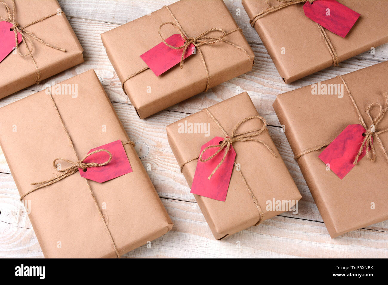 A group of plain brown paper wrapped Christmas presents on a white ...