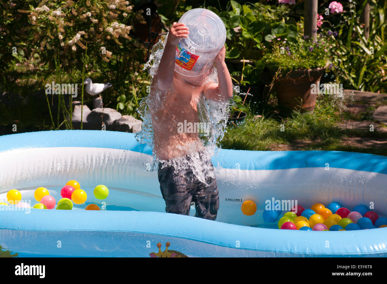 Child playing in a paddling pool in back garden stock for Best children s paddling pool