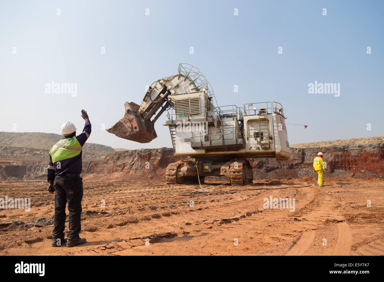 a supervisor guides and instructs an excavator operator during