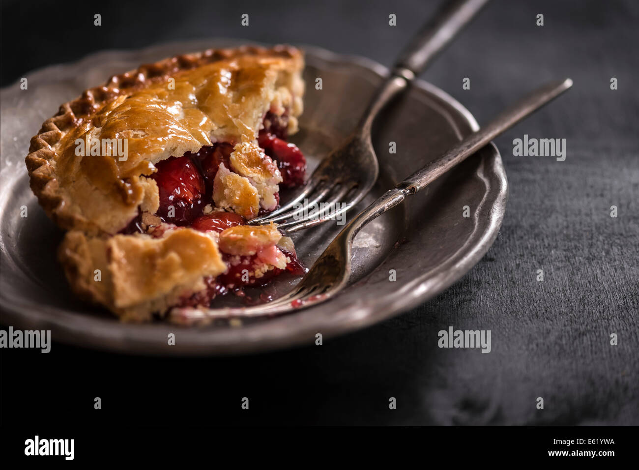 Small cherry pie on metal plate with antique forks. Dark moody setting & Small cherry pie on metal plate with antique forks. Dark moody ...