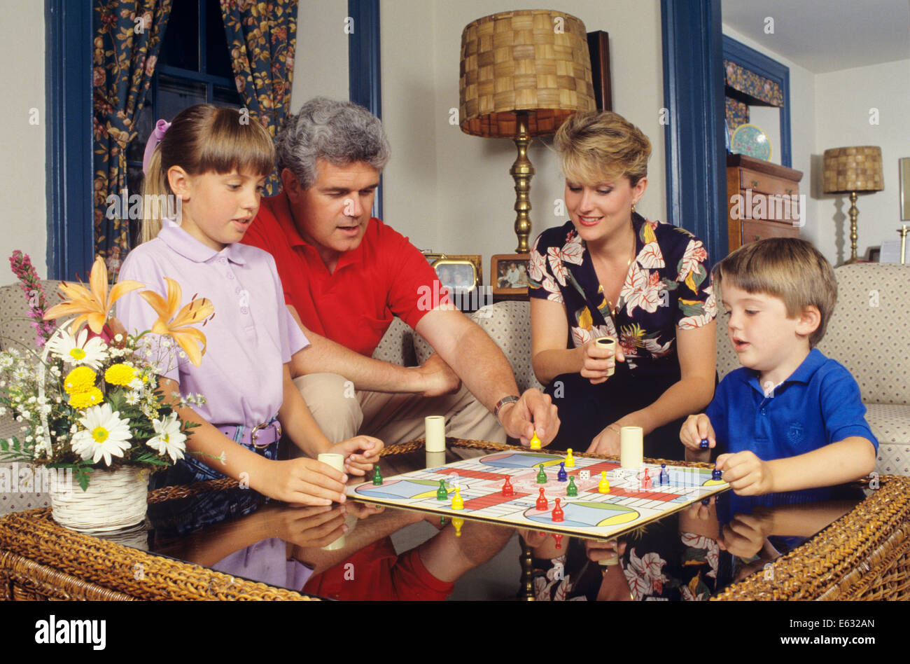 1980s 1990s engaged family of four playing parcheesi board game at stock photo royalty free. Black Bedroom Furniture Sets. Home Design Ideas