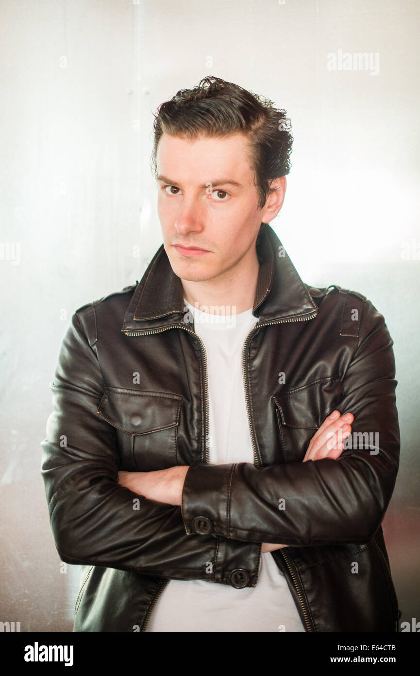A man wearing black leather jacket and white t-shirt dressed in ...