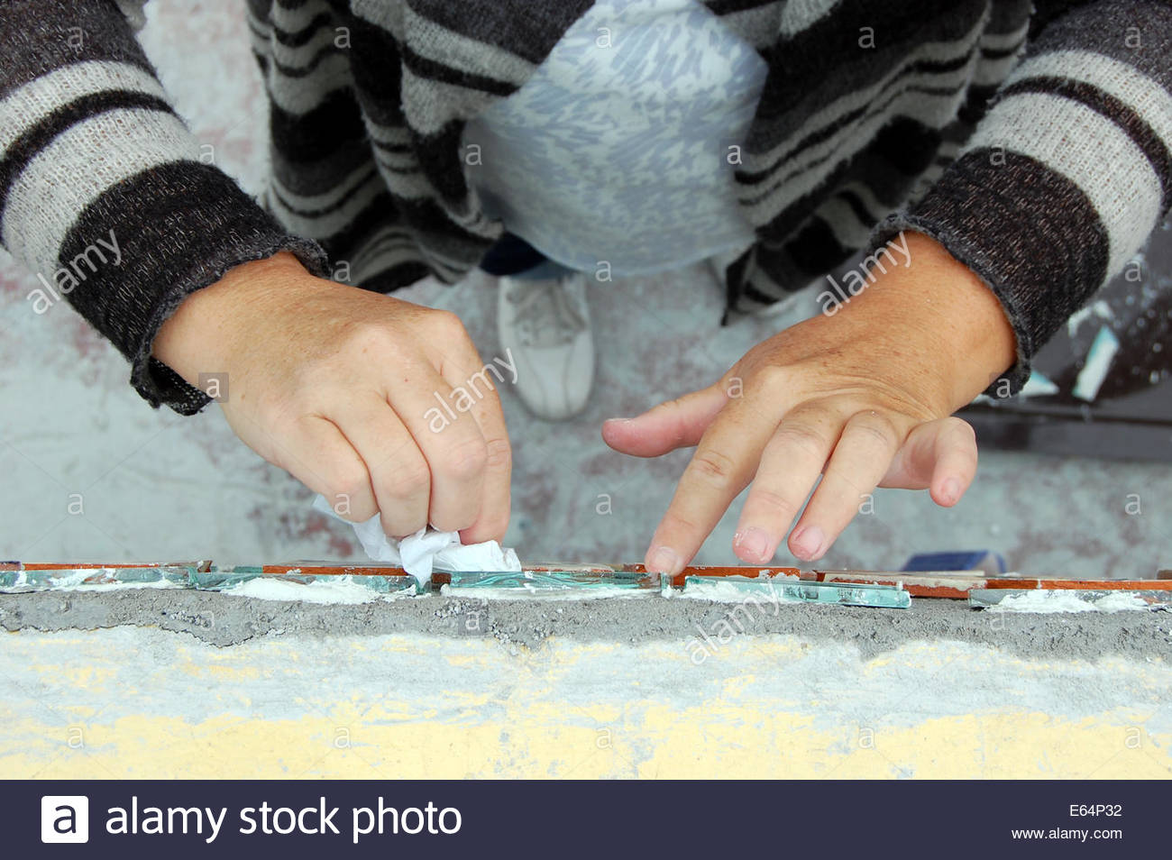 Closeup view of peoples hands doing arts and crafts ceramic tile closeup view of peoples hands doing arts and crafts ceramic tile mural work with plaster and grout dailygadgetfo Images