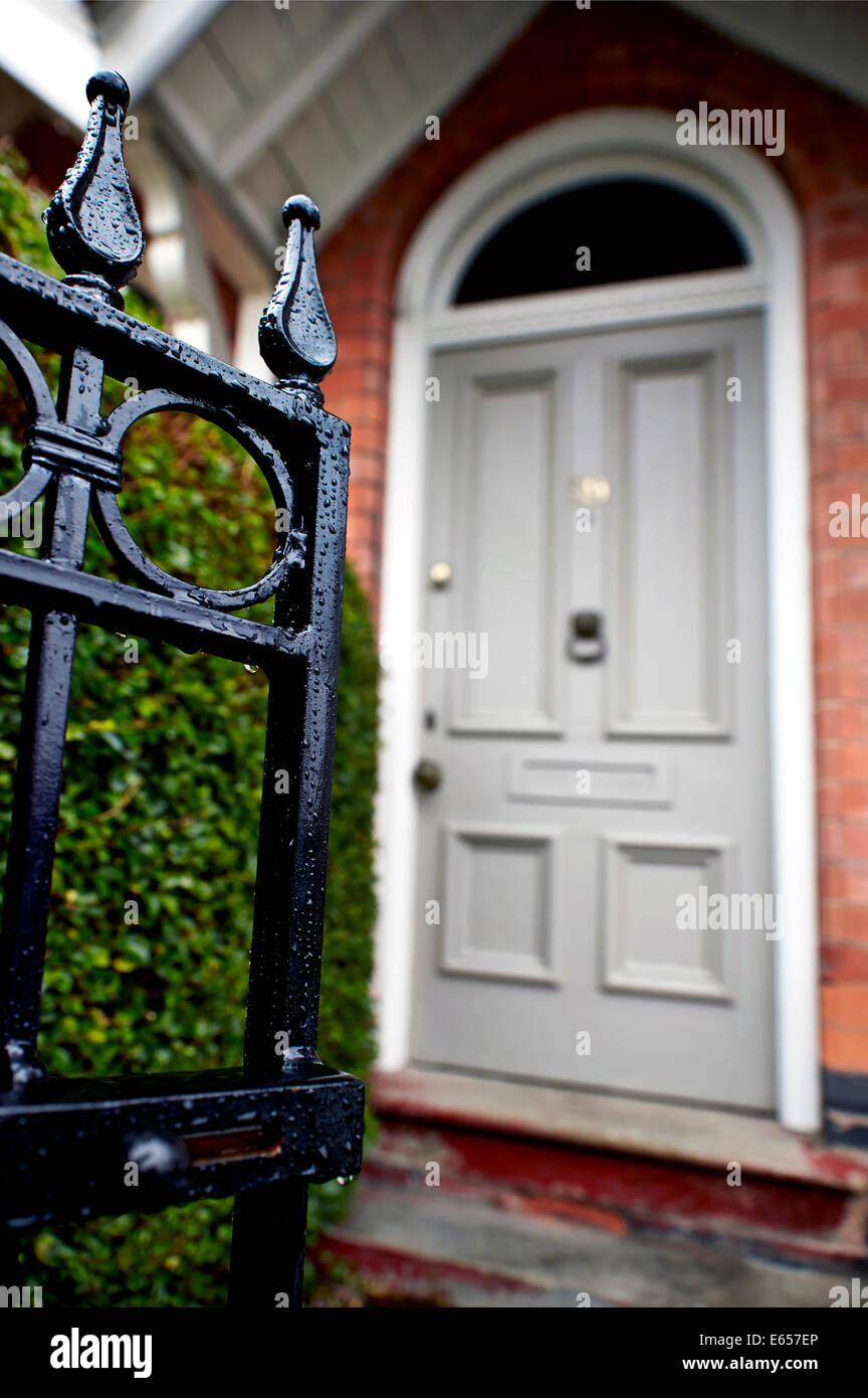An Open Front Gate Leading To A Hedge And Grey Front Door Of A Terraced  Victorian