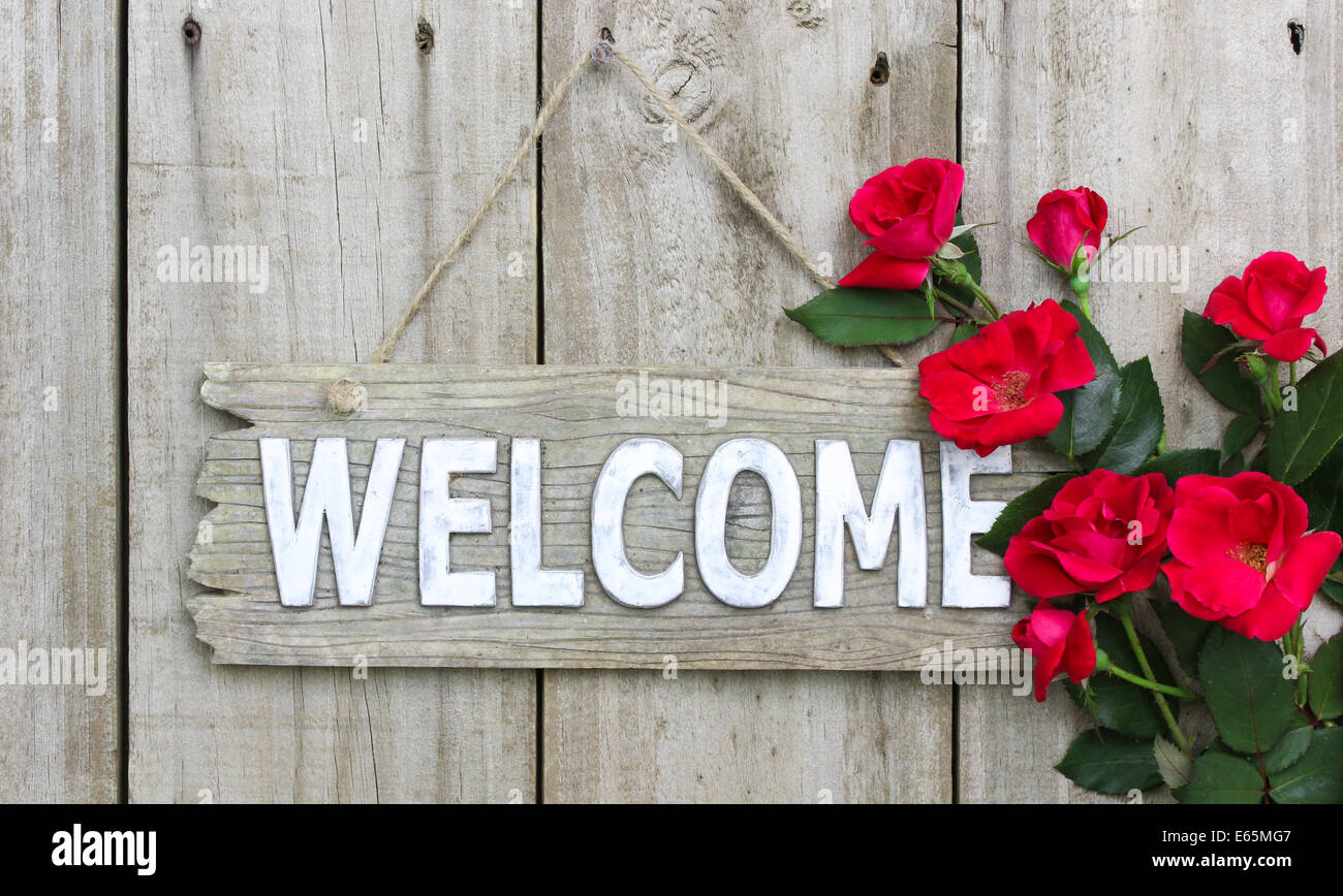 Distressed Welcome Sign Hanging On Wood Fence With Flower