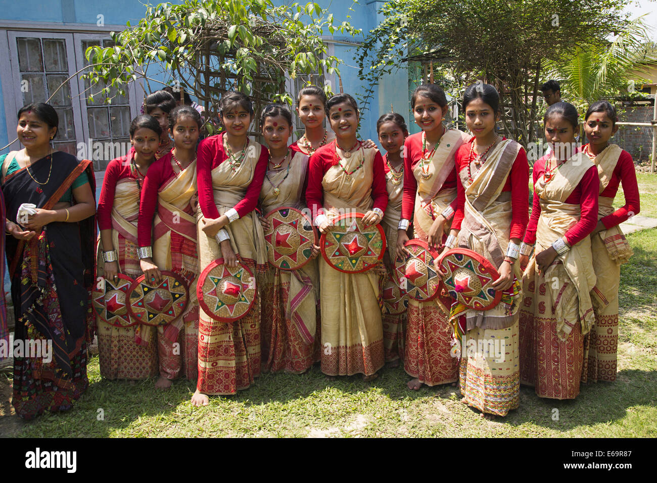 Young Assamese Girls In Traditional Dress Holding Sarudaya