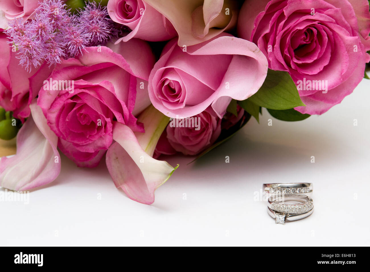 stock photo white gold and diamond wedding rings and an engagement ring are displayed on a white background next to pink wedding flowers - Pink Wedding Rings