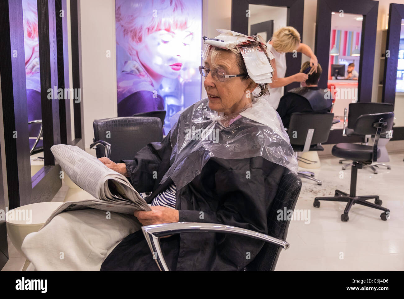 Older woman in hair salon reading newspaper while waiting for Reading beauty salon