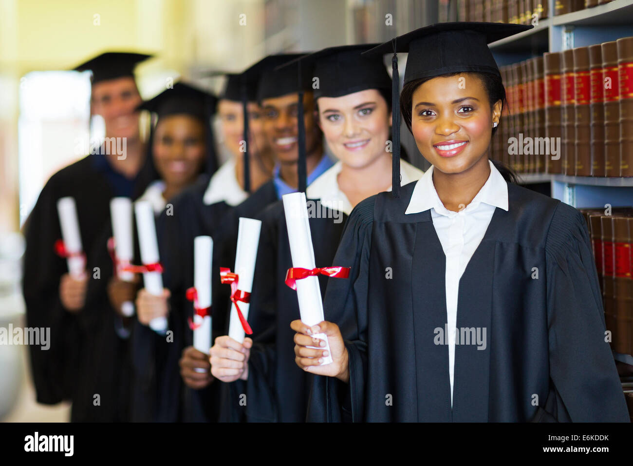 group of happy graduates holding diploma in library stock photo  group of happy graduates holding diploma in library