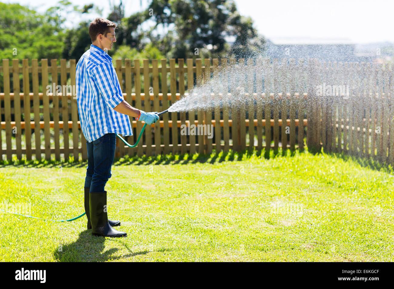 young man watering backyard lawn using hosepipe stock photo