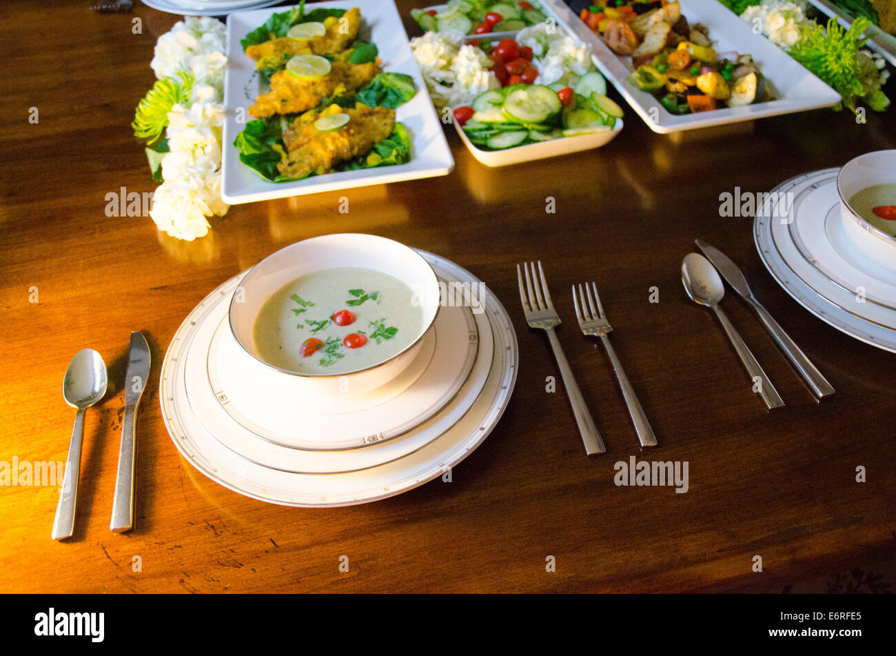 Buffet Style Dinner Party In An Elegant Setting With Soup Fish And Vegetables On A Wooden Dining Table Fancy White China