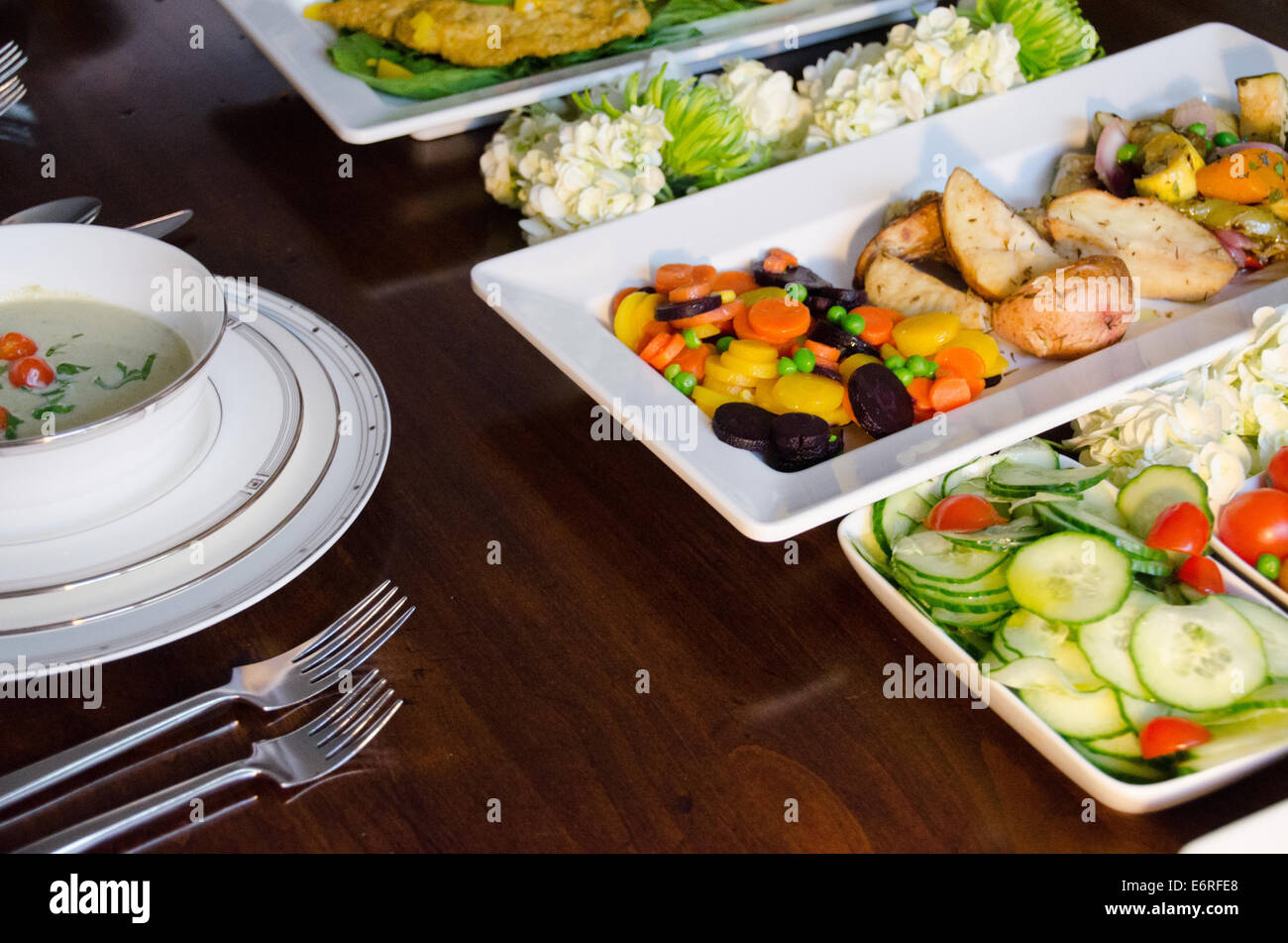 Close Up Shot Of A Buffet Style Family Dinner Party On Dining Room Table With Fish Soup Potatoes And Vegetables