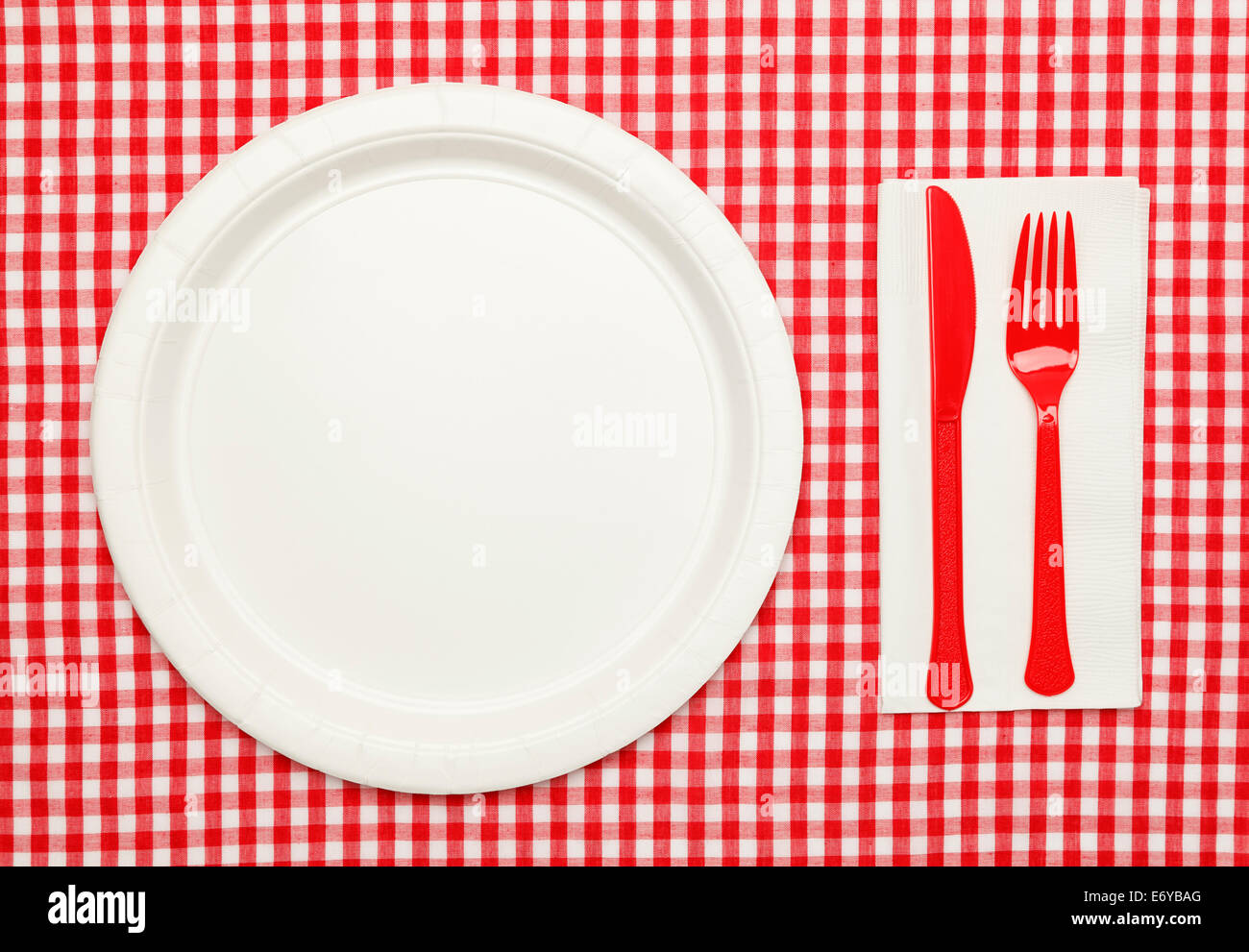 Paper Plate On Red Checkered Table Cloth Wtih Plastic Utnesils And Napkin.