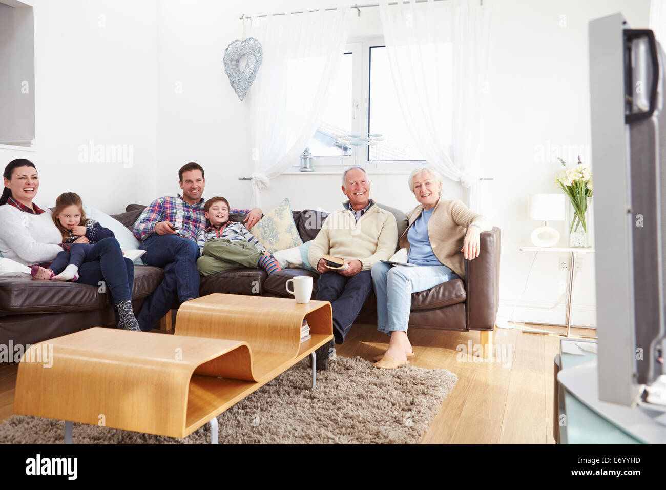 multi generation family watching tv together stock photo