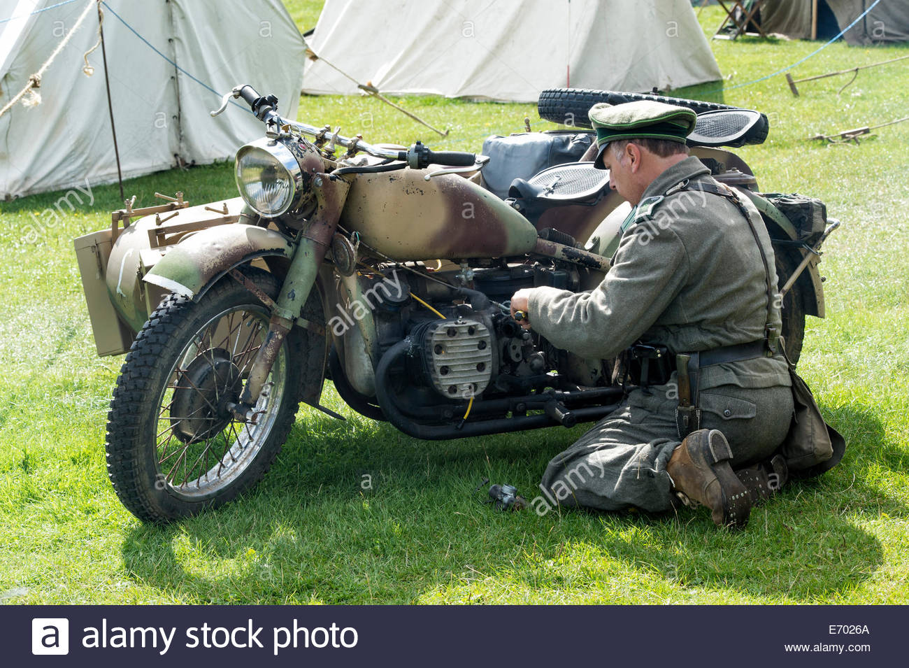 ww2 german army soldier fixing bmw motorcycle. historical re stock