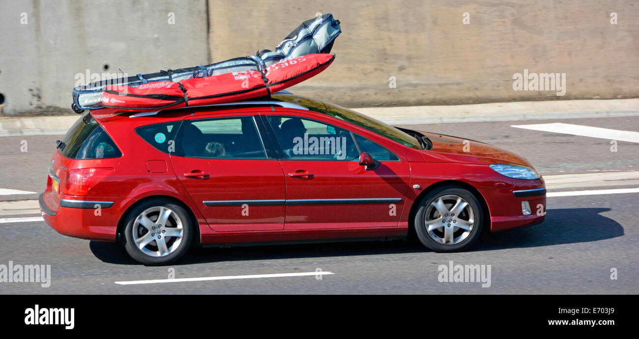 Car Driving Along Motorway With Roof Rack Loaded Luggage Bags Bending From Wind Pressure Cars