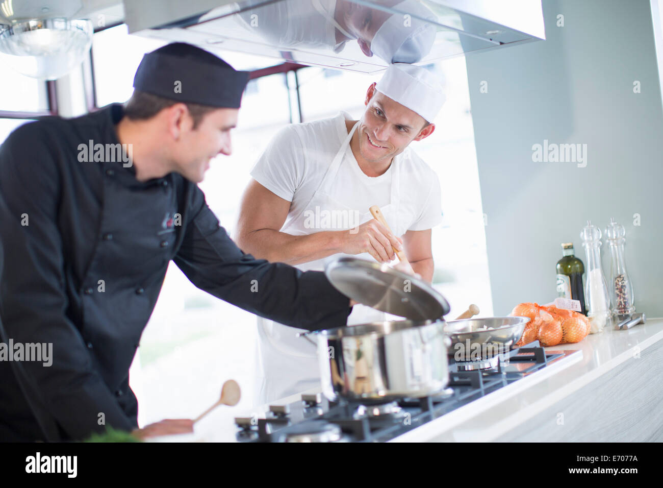 Kitchen Hobs Commercial ~ Two male chefs cooking on hob in commercial kitchen stock