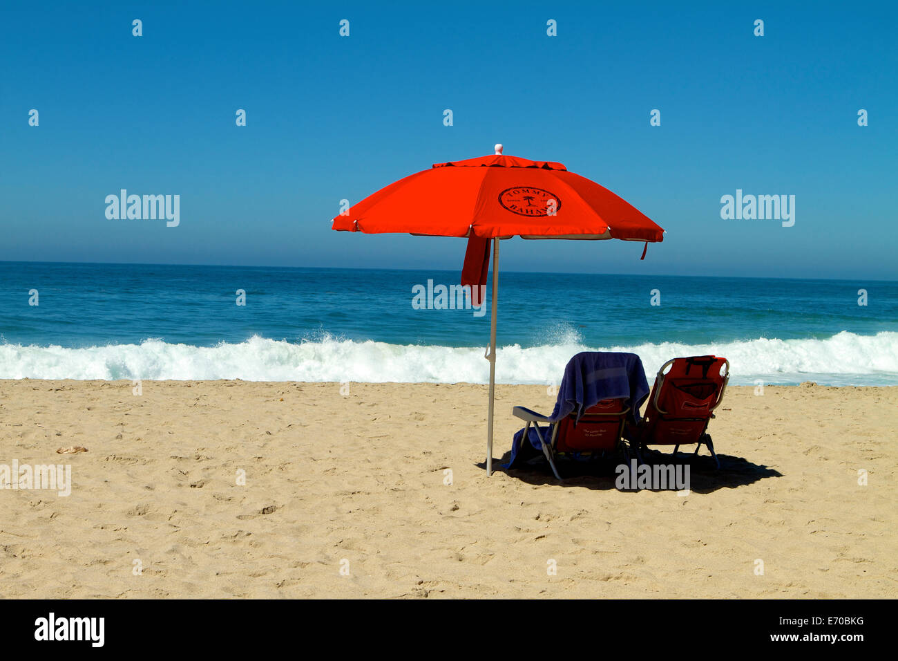 stock photo thousand steps beach in laguna beach california bright red tommy bahama umbrella with empty beach chairs - Tommy Bahama Chairs Beach