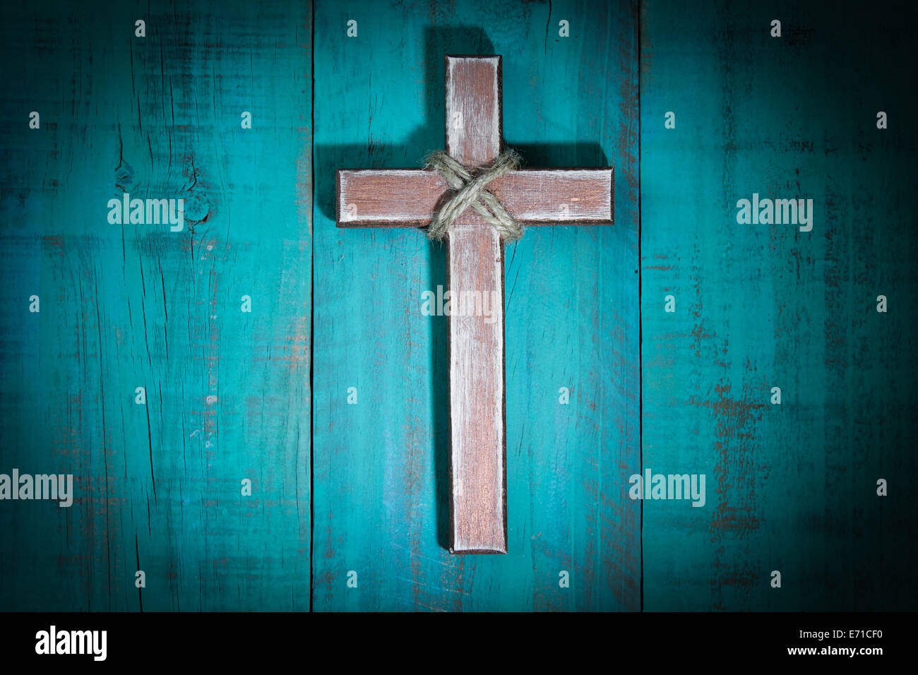 Spotlight On Rugged Wooden Cross Hanging On Antique Teal