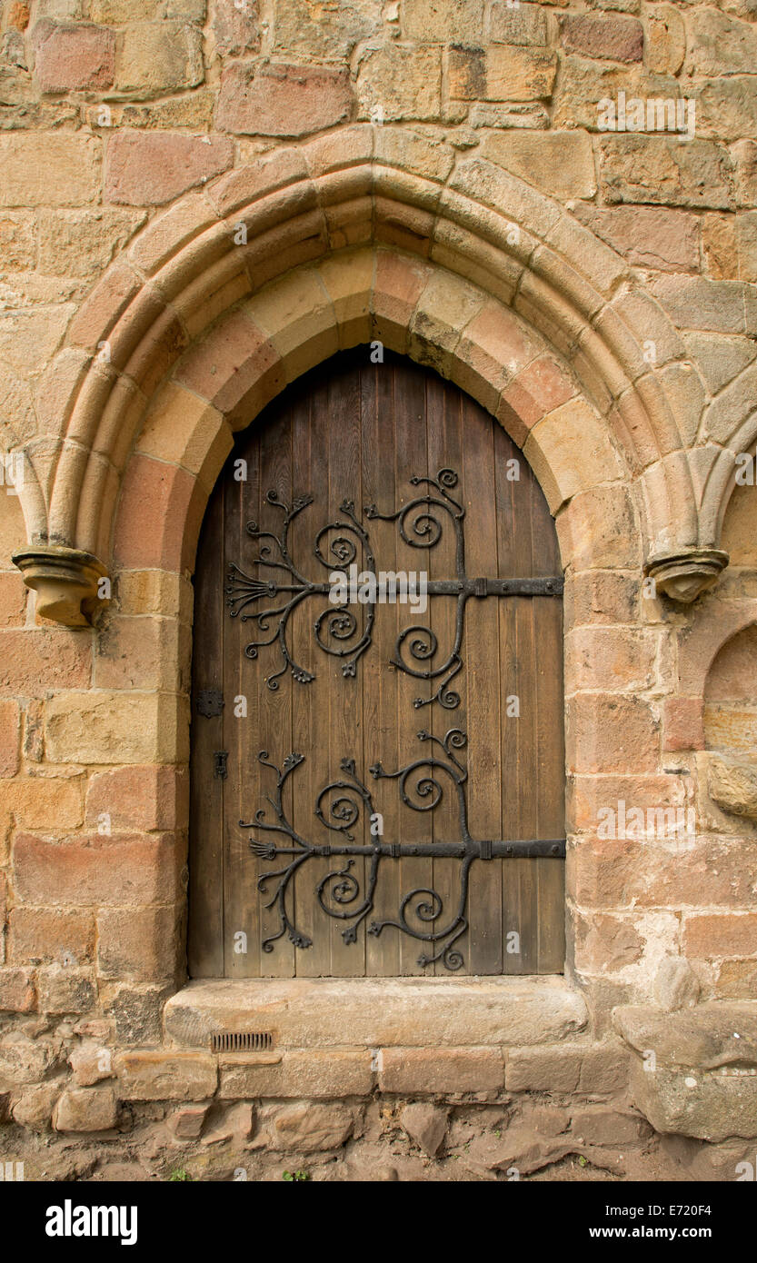 Arched wooden door with huge spectacular and decorative hinges in weathered stone wall at ruins of historic Bolton priory England & Arched wooden door with huge spectacular and decorative hinges in ...