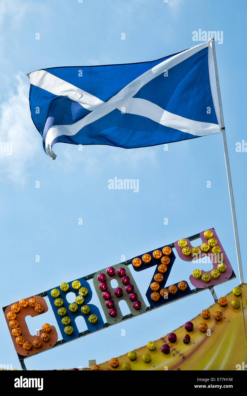 The saltire the scottish national flag flying atop a flagpole the saltire the scottish national flag flying atop a flagpole above the word crazy written in multi coloured fairground lights sciox Image collections
