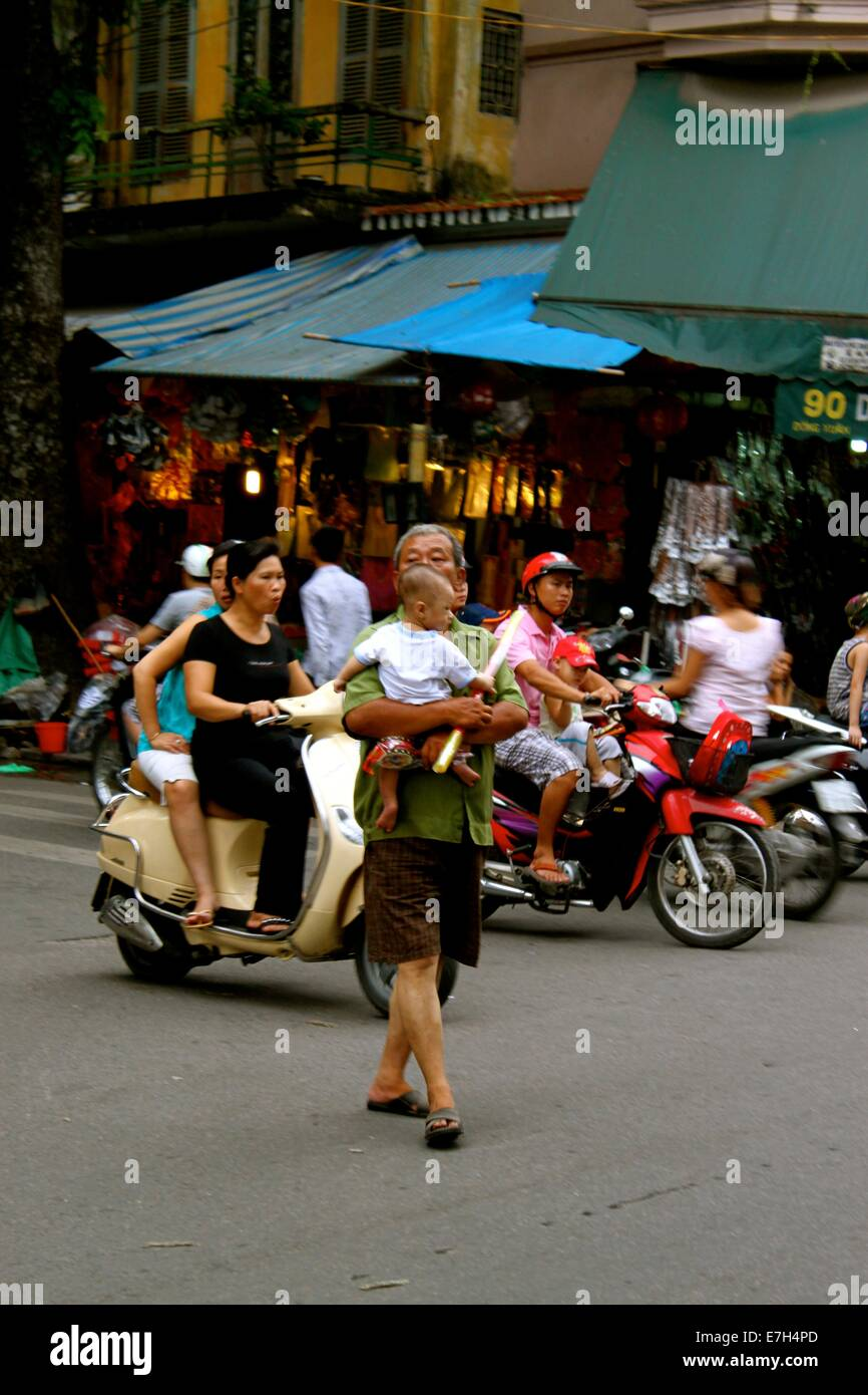 An elderly man carries a young child across a busy Hanoi ...