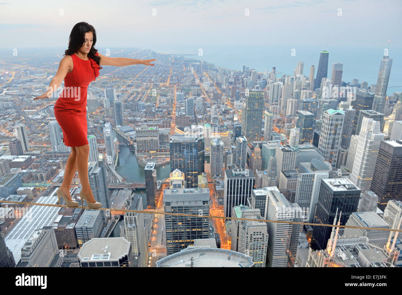 Businesswoman walking on tightrope with city in background ...