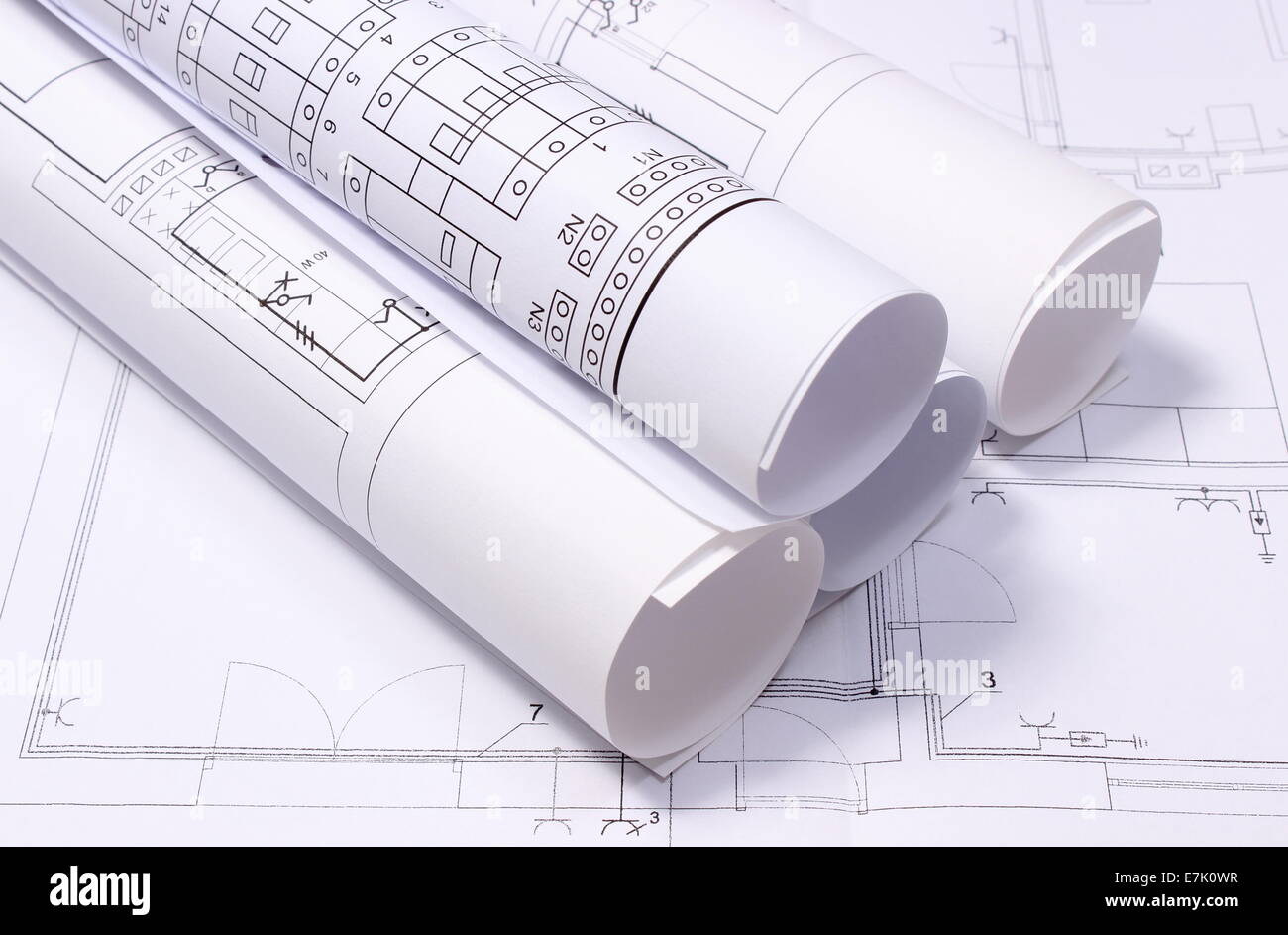 rolled electrical diagrams lying on construction drawing of house drawings for the projects engineer jobs