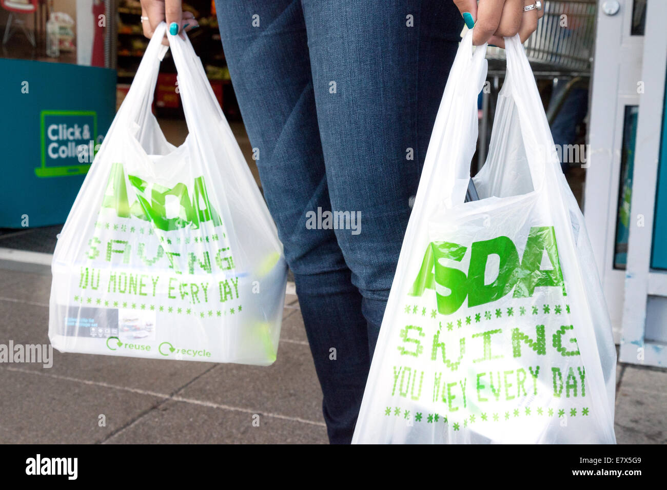 A woman carrying shopping bags from Asda supermarket, UK Stock ...