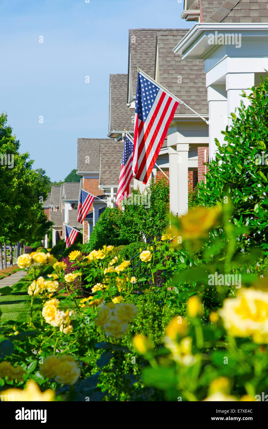 american flags hang from a front porches in a neighborhood