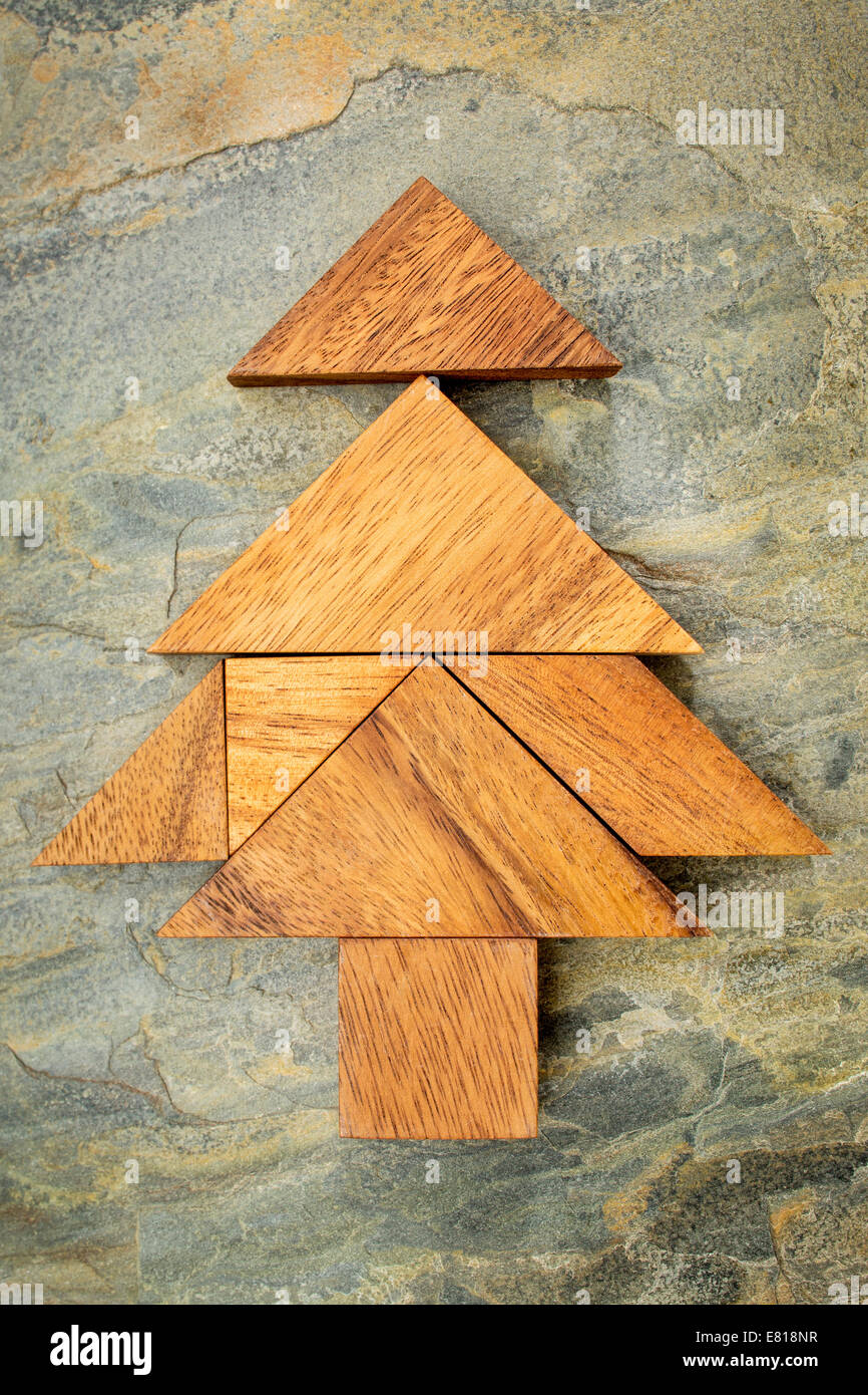 abstract picture of a christmas tree built from seven tangram wooden pieces over a slate rock background christmas holiday conc