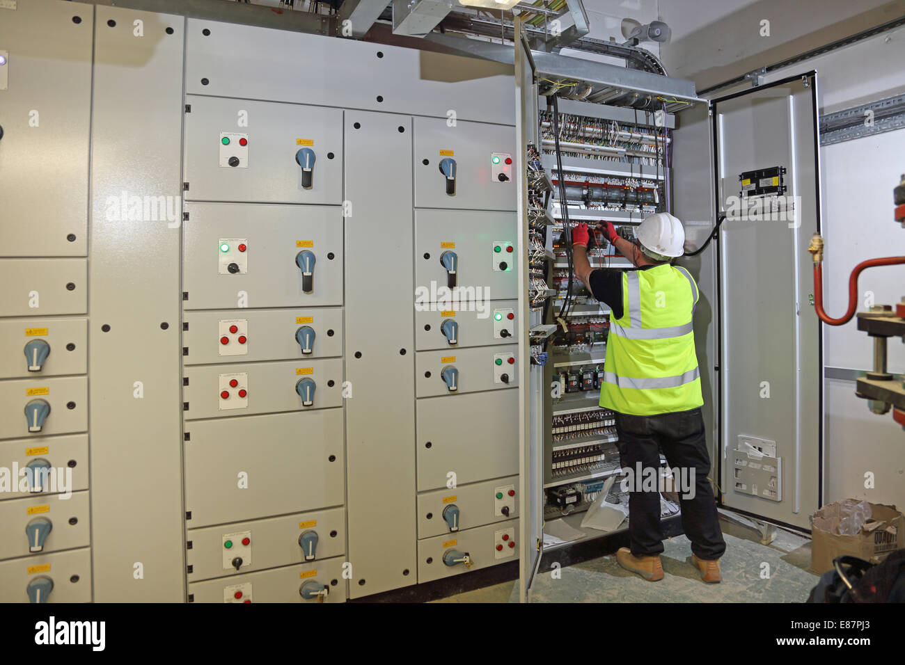 A building services engineer works in an electrical control ...