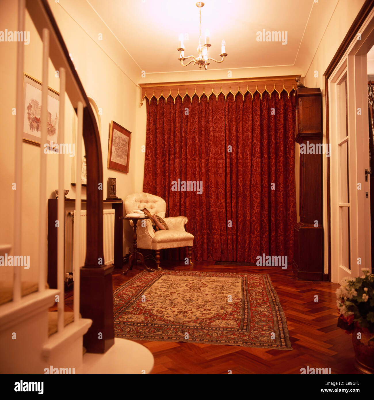 Gothic Wooden Pelmet Above Red Curtains In Traditional Hall With Armchair And Large Rug On Parquet Floor