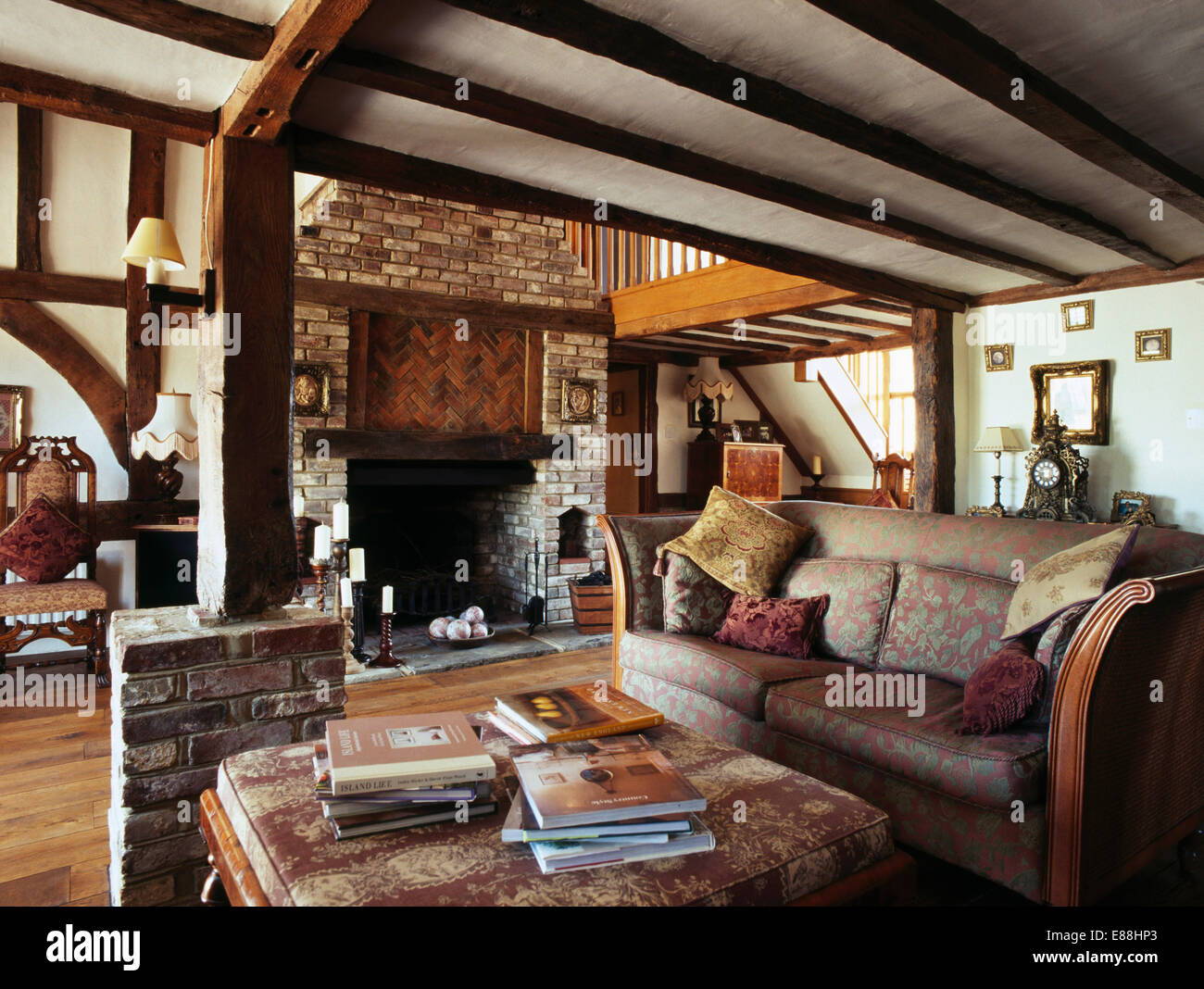 patterned sofa in living room with brick fireplace and exposed