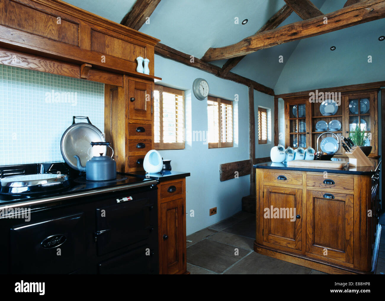 Blue Kettle On Black Aga In Pastel Country Kitchen With Stained Wood Units
